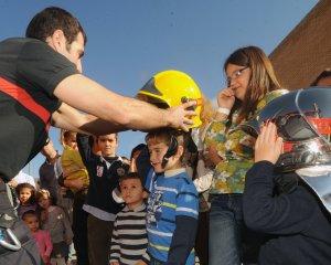Un bombero coloca un casco protector a un niño ante la divertida mirada del grupo. :: ISRAEL SÁNCHEZ/ AGM